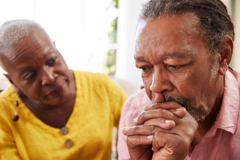 Senior African American woman comforting senior African American man