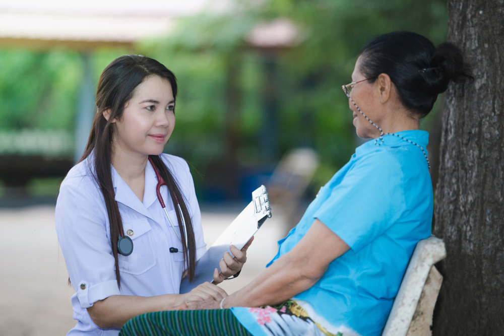 asian doctor talking to elderly asian woman